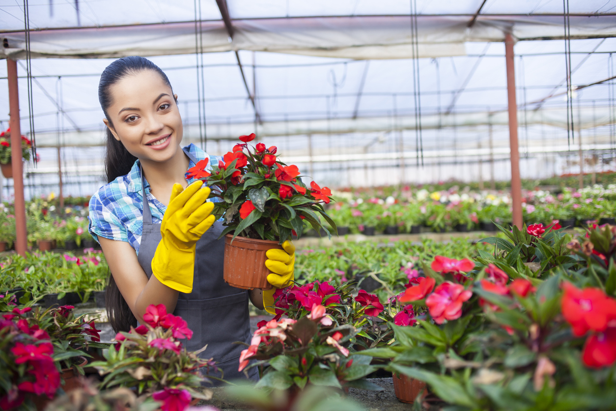 Young asian woman taking care of beautiful flowers